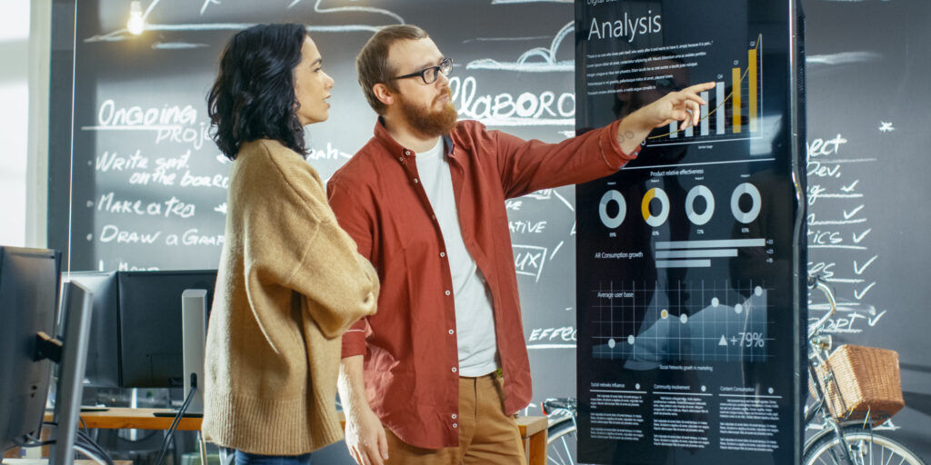 Female Developer and Male Statistician Use Interactive Whiteboard Presentation Touchscreen to Look at Charts, Graphs and Growth Statistics. They Work in the Stylish Creative Office.